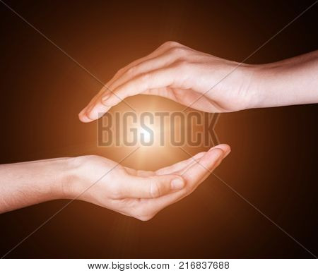 Woman hands protecting and containing bright, glowing, radiant, shining light. Emitting rays or beams expanding of center. Religion, divine, heavenly, celestial concept. Black background copy space poster
