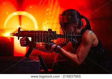 Young strong woman warrior shooting from machine gun in dramatic urban night scene. Tattoo on body.
