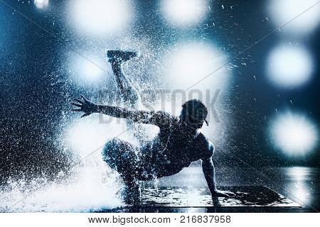 Young man break dancing in club with lights and water. Tattoo on body. Blue tint colors.