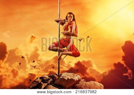 Young woman exotic style pole dancing with snake on mountain top. Asian style and red warm colors. Tattoo on hand.
