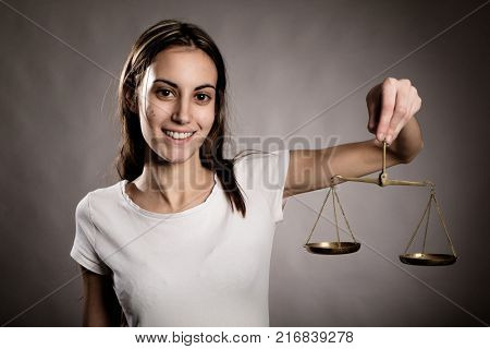 young woman holding a justice scale looking at camera