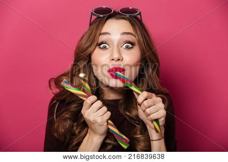 Close up portrait of a funny hungry attractive girl wearing sunglasses eating candy isolated over pink background