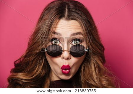 Close up portrait of a shocked pretty girl wearing sunglasses looking at camera isolated over pink background