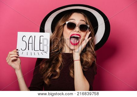 Portrait of a cheerful pretty girl wearing hat and sunglasses screaming and showing sale banner isolated over pink background