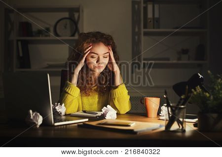 Tired business woman in office at night. Girl suffering from headache, working late, solving a problem at workplace with crumpled papers, gadgets and notepad, copy space. Overworking concept