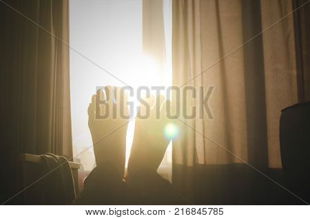 Male legs opposite the sunlight from the window. A man is resting on the couch.