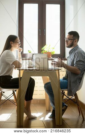 Young businesswoman and businessman sitting at meeting and discussing new working concept. Millennial employees negotiating in office. Vertical image