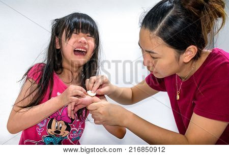 BANGKOK THAILAND - DECEMBER 01: Girl at home cries in pain as the mother tends to her wound in Bangkok on December 01 2017.