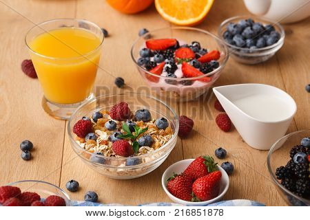 Tasty breakfast with muesli, fresh berries, milk jar, black coffee and orange juice. Low fat morning meals and healthy start of the day. Detox and diet concept
