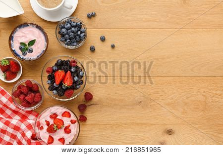 Tasty breakfast with light greek yogurt, fresh strawberries, raspberries, blueberries and blackberries. Low fat morning meals and healthy start of the day. Detox and diet concept, top view, copy space