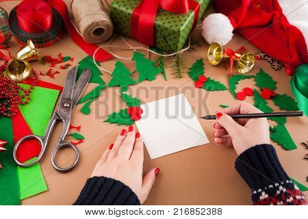 Creative diy craft hobby. Woman writing greeting card for Christmas on table with felt sheets and scraps, scissors and holiday decorations. Closeup of female hands at craft paper background.