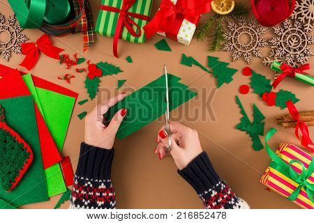 Creative diy craft hobby. Woman makes christmas tree decoration on table with felt sheets and scraps, scissors and trappings. Closeup of female hands at craft paper background.