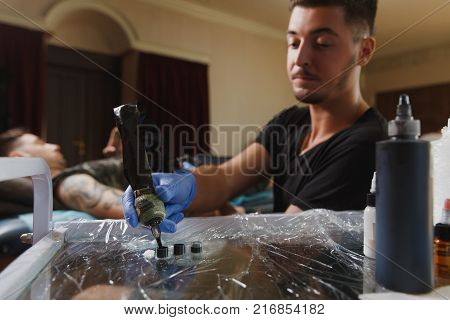 Close Up Of Professional Tattooer Artist Doing Picture On Hand Of Man By Machine Black Ink From A Ja