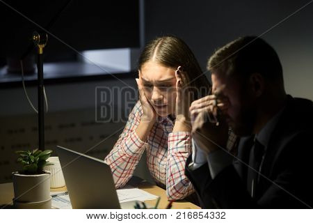 Depressed unhappy businessman and businesswoman having night shift in office and worried about work problem. Overwork, deadline, bankrupt work concept.