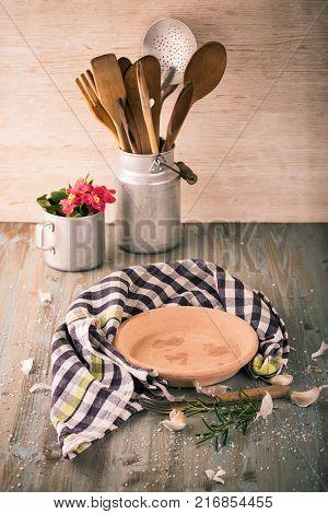 Empty Clay Plate On Wooden Board With Kitchen Utensils Around