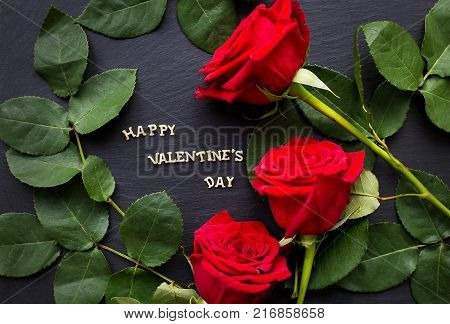 Gift by St. Valentine's Day, heart from threads and a red greeting card with an inscription of Happy Valentines day on a fabric linen backgroundThe inscription Happy Valentine on a black background with red roses