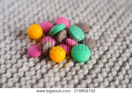many multi-colored tablets and vitamin close-up on a knitted background