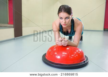 Two girls at gym perform exercises with suspension straps, fitness workout, selective focus