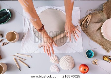 male potter master rolling up the clay on table with ceramic products. Front view, closeup portrait, focus on table. Art and business, hobby and freelance working concept.