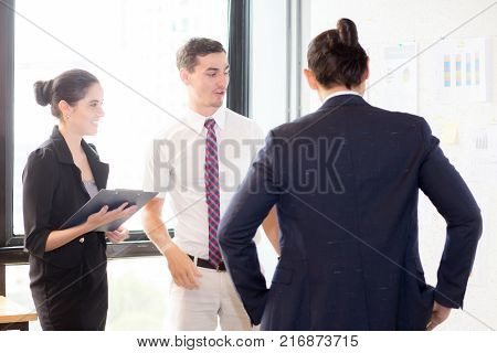 young businesspeople pointing towards graph with present profit while giving presentation in office teamwork concept.