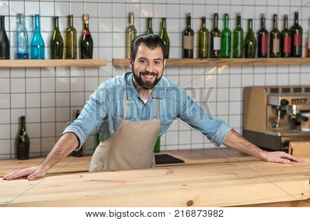 Ready. Enthusiastic positive professional waiter feeling good while being at work and standing with his hands on a bar counter with various bottles behind his back
