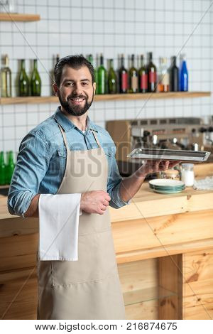 Cheerful waiter. Skilled bearded smiling waiter looking confident while being at work and being ready to bring the order with a tray in his hand