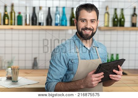 Convenient gadget. Positive emotional bearded waiter looking glad while standing with a modern convenient tablet in his hands and smiling