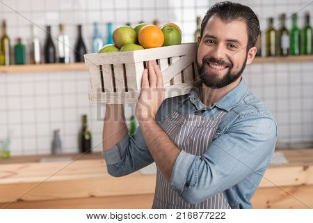 Fresh fruit. Handsome responsible enthusiastic worker looking not tired while holding a heavy wooden box with tasty fresh fruit and smiling cheerfully