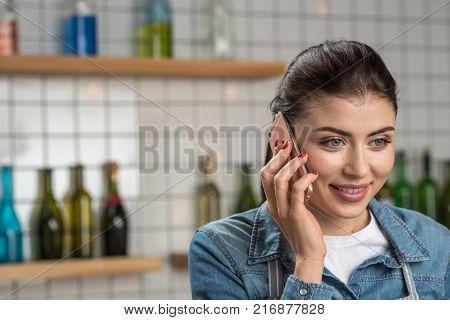 Good news. Pretty pleasant young woman standing in a nice cafe and looking interested while talking on the phone with her close friend and smiling