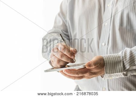 A Business Man Is Using His Cellphone And Stylus Pen.