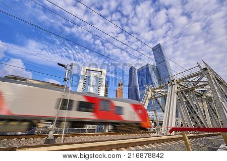 MOSCOW, AUG, 22,2017: View on moving passenger high speed train on metal bridge and Moscow biggest business center Moscow City skyscrapers towers buildings. Cityscape running new modern passenger train in front of Moscow-city business center