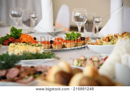 Holiday luxury table with gourmet food. New year's eve feast with delicious dishes. The anniversary of the restaurant.