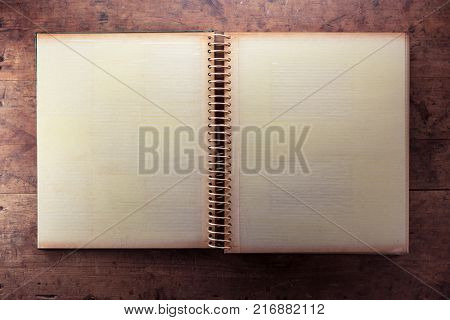 Blank page of an 1970s photo album, in retro tone, on a dark well used rustic wooden table.