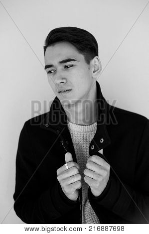 Young man looking at camera and holding the coat lapels. Model posing