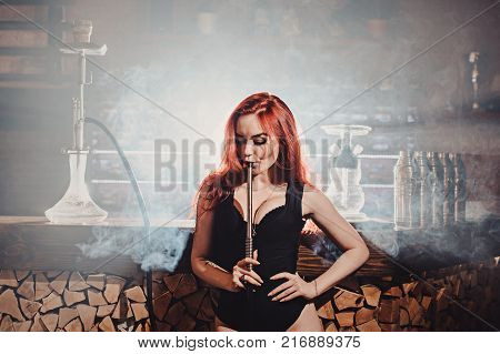 Red-haired Sexy Girl In A Cafe Smoking A Hookah Dressed In Black Body