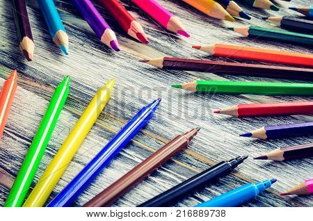 Colorful school supplies. Group of markers and crayons on a wooden table.