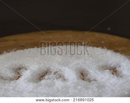 salt granules interspersed with wooden plate. for healty life