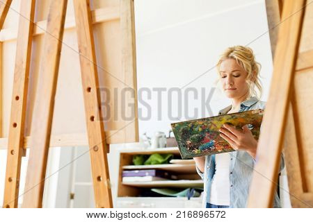 art school, creativity and people concept - woman with easel and palette painting at studio