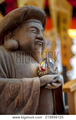 CRYSTAL ORB: A wooden monk statue at Kiyomizu Dera Temple holds a crystal orb in his hand, symbolizing prosperity and good fortune blessed to all worshipers.