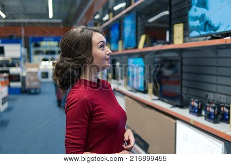 Smart modern female customer choosing large TV-sets at electronics store. She looks wondered. New screen generations.