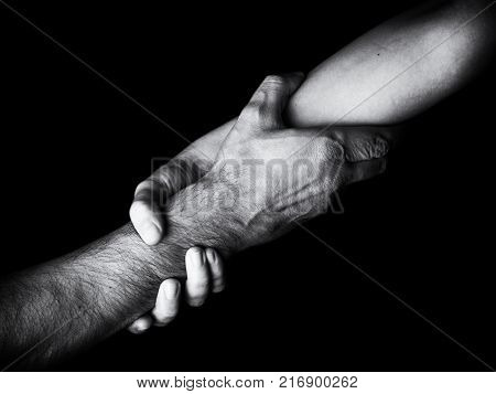Woman saving, rescuing and helping man by holding or griping the forearm. Female hand and arm pulling up male. Concept of rescue, love, friendship, support, teamwork, partnership, reaching, couple