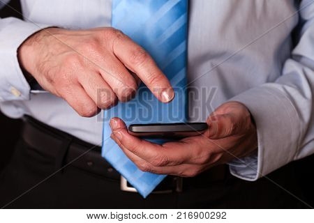 Man holding and touching screen or display with finger of a mobile phone, cell phone or smartphone. Male businessman typing a message or browsing the internet for apps on wireless digital device