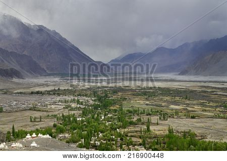 Wide mountain valley of Nubra, along the bottom of the river, green trees are green along the riverbed, in the foreground on the platform are white Buddhist stupas, fog, Northern India.