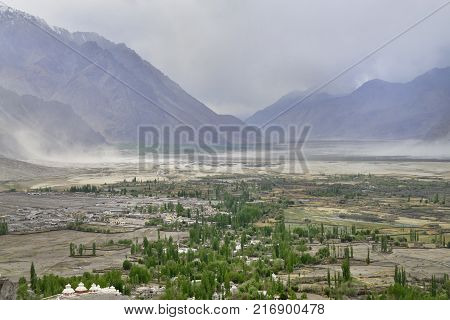 Sandstorm in a wide wide mountain valley: in the foreground there are magnificent expanses with a river, green trees and white Buddhist stupas, in the distance the bluish mountains with whirlwinds.