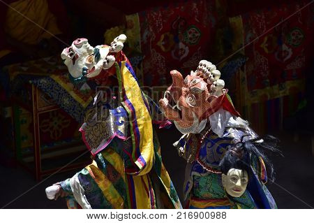Two Buddhist lamas in the courtyard of the monastery in sacred masks of white and orange, the Masks of orange color in the hands of a model of a severed human head. Ancient Tibetan ritual.