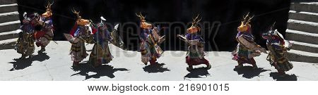 Tibetan dance of Buddhist Lama in Masks Yellow Reindeer and Blue Reindeer and sacral robes, Himalayas, Northern India, photo panorama.