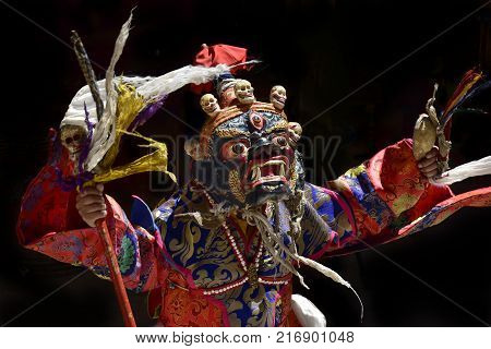 Ancient Tibetan sacral mask Palden Lhamo: a blue mask with small human skulls, bright red flags at the top, a wand in hand, the Himalayas.