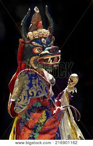 Buddhist monk in ritual Tibetan clothes and a sacred Mask of the bull with high sharp horns, whose name is Chojal, performs the Cham Dance.