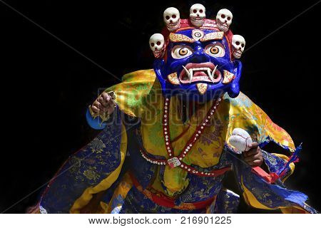 Buddhist lama in a ritual Tibetan costume and a mask of Blue Mahakala perform the sacred Cham Dance.