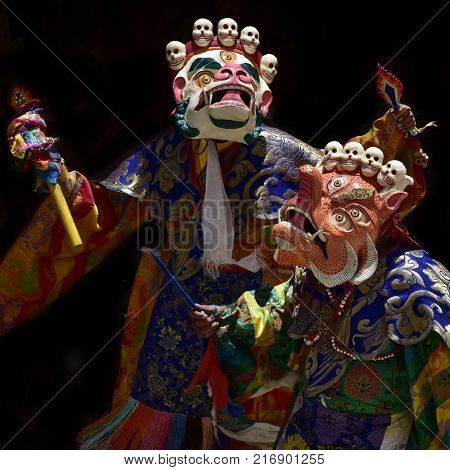 Two Buddhist monks in ancient ritual masks: the white mask of Mahakala and the orange mask of Makar, the masks are decorated with small human skulls.
